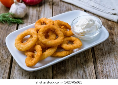 Onion rings in batter on white plate