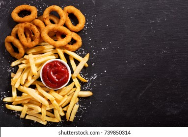 onion rings and french fries with ketchup on dark table, top view