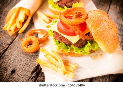 Onion rings,beef burger and french fries on the table.Selective focus on the onion ring and burger