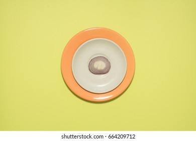 Onion slice on white and orange plate over lime green colored background