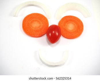 Onion sliced, Carrot sliced, Tomato sliced with face form on white background, fresh vegetables