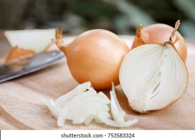Onion and slices on wooden cutting board.