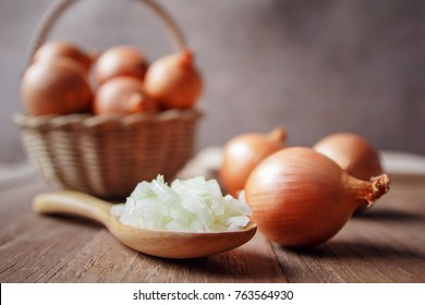 Onion and slices in wood spoon for cooking.