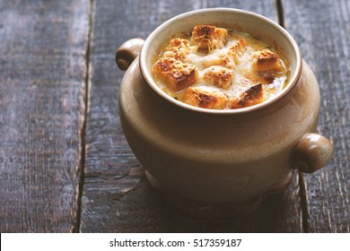 Onion soup in the ceramic pot on the wooden table horizontal