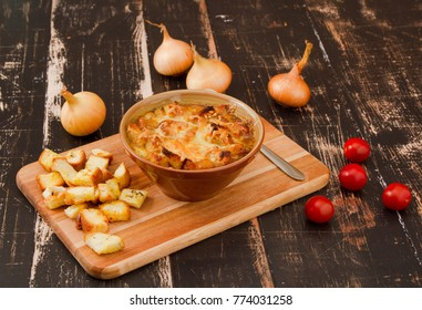 Onion soup with garlic toasts on wooden background
