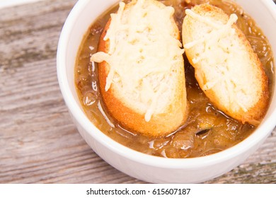Onion soup with toast on a wooden background