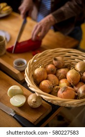Onions in a basket. Woman preparing food in kitchen, slicing vegetables.