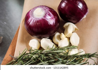 Onions and garlic lie on the wrapping paper on the kitchen table. Cooking food, clode-up.