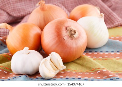 Onions and garlics on colorful towel.