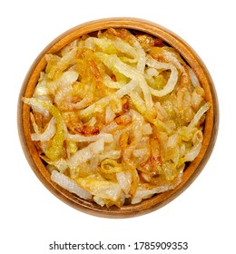 Onions, golden brown roasted, in a wooden bowl. Sliced white onions, fried in oil to get a nice color and fully aroma. Allium cepa. Closeup from above, on white background, isolated, macro food photo.