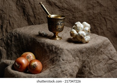 Onions and group of garlics with mortar and sack backgrounds