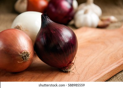 Onions. Various onions on a board on a background sacking, burlap. Garlic and onion. Violet onions. Garlic.