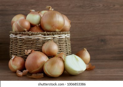 Onions in a wicker basket and next to it. A lot of onions in wicker vessels. Onions for cooking. Onions of different sizes. Vegetables for a healthy diet.