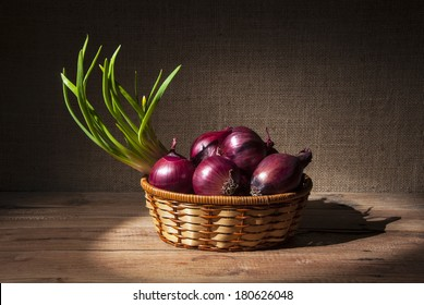 Onions in a wicker basket on a wooden table
