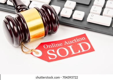 Online auction sold tag with wooden gavel on computer keyboad.