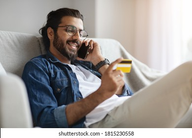 Online Banking. Handsome Indian Man Talking On Cellphone And Using Credit Card And At Home, Paying In Internet, Making Shopping Or Money Transfer, Managing Bills, Sitting On Couch In Living Room
