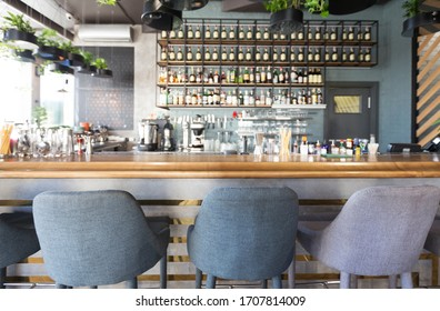 Online bar. Bar counter with soft chairs in cafe with no visitors, blurred background, panorama, copy space