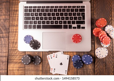 Online betting or poker. Top view of a computer with chips and cards for betting or playing. Online game concept.