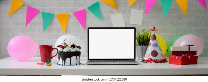 Online Birthday celebration concept with blank screen laptop, cake and decorations on white table