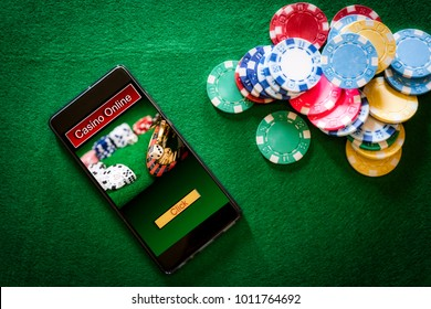 online casino smartphone with poker chips device over green table. Concept about entertainment and gambling