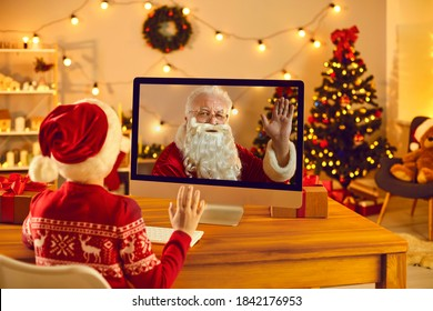 Online celebration and wonderful surprises. Little boy in Santa hat video calling Father Christmas and waving hand at computer screen sitting in cozy room with decorated tree and lights at home - Shutterstock ID 1842176953
