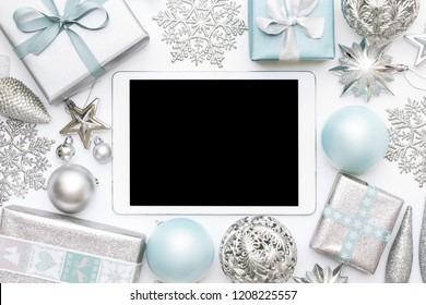 Online Christmas Shopping. Boxing Day Sale Background. Wrapped christmas presents, ornaments and blank screen digital tablet isolated over white background.