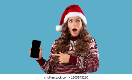 Online Christmas shopping. Shocked young girl in Santa hat pointng at mobile phone with empty screen, blue background. Panorama