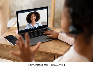 Online Class. Black Schoolgirl At Laptop Waving Hand Greeting Teacher On Computer Screen Learning At Home. Selective Focus