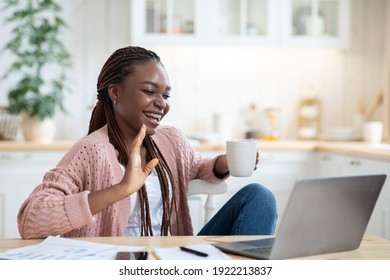 Online Communication. Cheerful Black Female Freelancer Talking At Laptop Camera And Drinking Coffee, Relaxing In Kitchen At Home, Smiling African American Lady Enjoying Pleasant Conversation