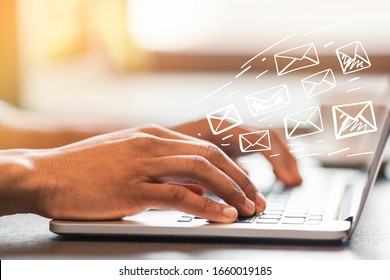 Online communication concept. African American man typing and sending e-mails in office, design with envelope icons
