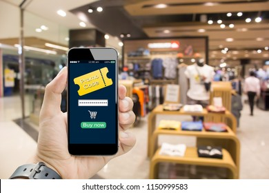 Online Discount coupon promotion code concept.Hands holding mobile phone on blurred shopping mall as background