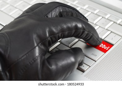 Online distributed denial services attack  concept with hand wearing black leather glove pressing enter key on metallic laptop keyboard