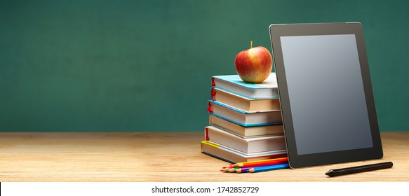 Online education. Books and tablet on the desktop on blackboard background. Copy space for text