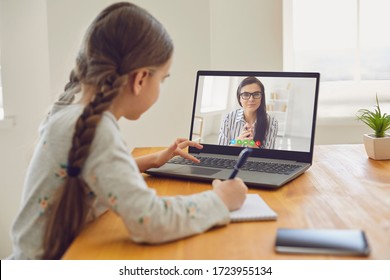Online education of children. Girl schoolgirl teaches a lesson online using a laptop video chat call conference with a teacher at home.