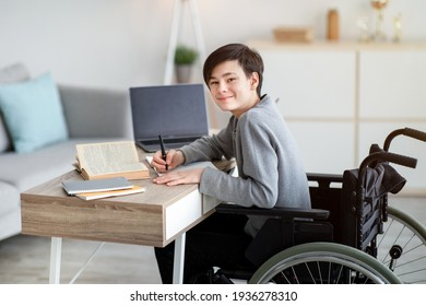 Online education for dsiabled teens. Happy teenage boy in wheelchair studying online from home, copy space