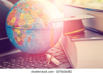 Online education or online learning concept : Graduation cap, a globe map and books, depicts knowledge can be learned online anywhere and everywhere, even in universities or campus around the world.