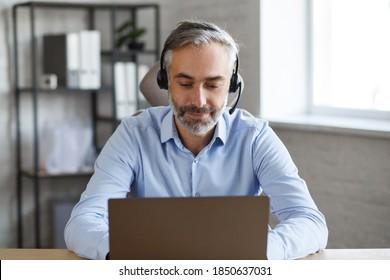 Online-Bildung, Fernarbeit, Heimunterricht. Portrait von grauhaariger, gut aussehender Mann, der online unterrichtet. Online-Treffen, Videoanruf, Videokonferenz, Kurse online.