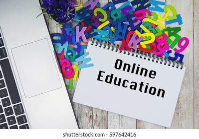 ONLINE EDUCATION text on notebook with laptop and piles of alphabet on wooden table.