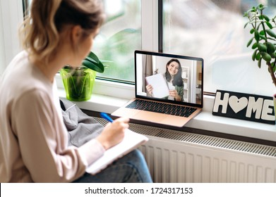 Online education. Young attractive girl is engaged in an individual lesson with a teacher on video communication using a laptop. Distant learning