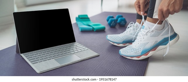 Online fitness class at home banner. Woman getting ready to train hiit workout with laptop screen for streaming. Tying her shoe laces panoramic.