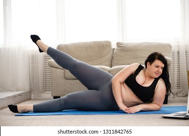 online fitness class, home training, technology and diet. overweight woman exercising under the supervision of a personal trainer using laptop in living room