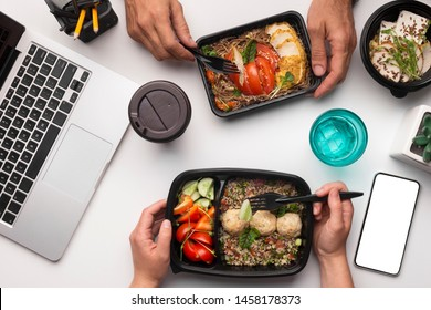 Online food delivery. Healthy lunch at office workplace with colleague, cellphone with blank space