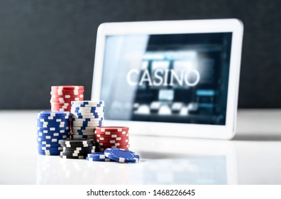 Online gambling on mobile casino concept. Stack of poker chips and tablet with slot machine on screen. Betting on internet and playing digital games for money with electronic device.