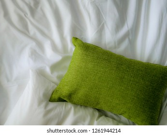 Online hotel room booking concept space : Lazy Sunday morning on crumpled white bed with pastel green pillow