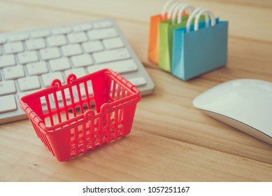 Online internet global shopping, worldwide e-commerce concept - red basket, shopping bag with keyboard and mouse on desk