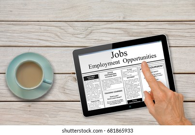 Online job hunting Hand with computer tablet reading employment ads on table with coffee