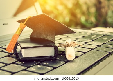 Online learning or e-learning and online graduate certificate program concept : Black graduation cap, diploma on a laptop computer keyboard, depicts distant learning can be done via cyber or internet.
