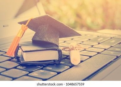 Online learning or e-learning and online graduate certificate program concept : Black graduation cap, diploma on a laptop computer keyboard, depicts distant learning can be done via website / internet