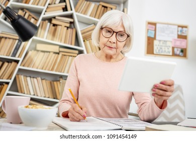 Online lecture. Attentive senior woman using tablet while taking notes