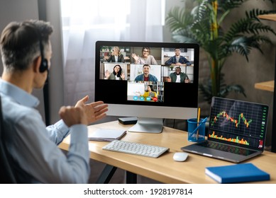 Online lesson or business webinar. Successful man sits at the work desk, on a computer screen are different multiracial people and teacher gathered in an online lecture by video conference